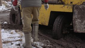 Workers walking in front of forklift stucked in deep mud. Unrecognisable workers walking on snow in front of forklift stucked in deep mud, winter day stock video footage