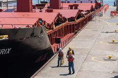 Workers walking beside large freighter. Sault Ste. Marie, Michigan/USA - June 26th, 2013: Group of workers walking beside large ship as it passes through the soo stock photo