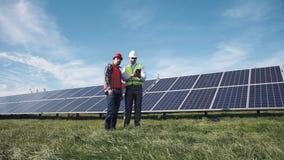 Workers walking in between rows of solar panels stock video footage