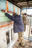 Workers walling the house with wall siding Stock Images