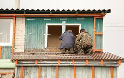 Workers walling the house with wall siding.  Royalty Free Stock Images