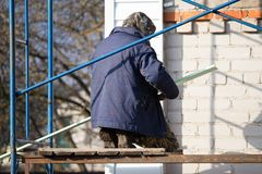Workers walling the house with wall siding.  Stock Images
