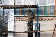 Workers walling the house with wall siding.  Stock Image