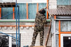 Workers walling the house with wall siding Stock Photography