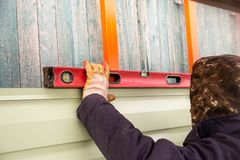 Workers walling the house with wall siding.  Stock Photos