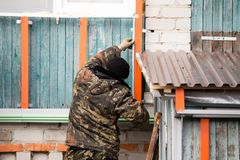 Workers walling the house with wall siding.  Stock Photo