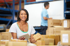 Workers In Warehouse Preparing Goods For Dispatch. Male And Female Workers In Warehouse Preparing Goods For Dispatch Smiling To Camera stock photography