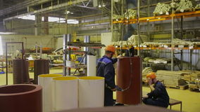 Workers in a warehouse puting products on places using industrial crane. stock video footage