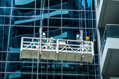 The workers wash the modern office buildings. Department stores Stock Images