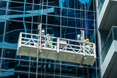 The workers wash the modern office buildings. Department stores Royalty Free Stock Photos