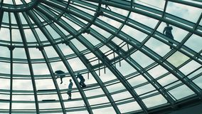Workers washing the roof made of glass of a modern office building stock footage