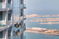 Workers washing windows at height, modern skyscraper. Window cleaners working on high rise building in Dubai Royalty Free Stock Photo