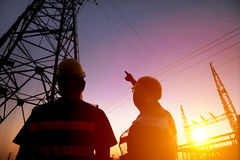Workers watching the power tower and substation with sunset b Royalty Free Stock Images