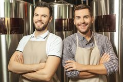 Workers wearing aprons with crossed hands stock photos