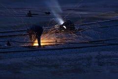 Workers welders repair metal rails. The workers welders repair metal rails Stock Photo