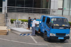 The workers were unloading the building materials from the car Stock Image
