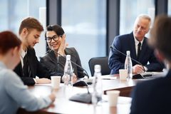 Workers Whispering in Business Meeting stock photos