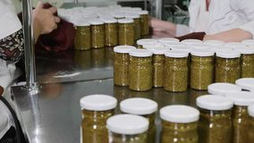Workers wipes a glass jar with pesto sauce before branding at conveyor, close-up