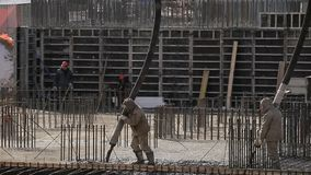 Workers work at building, fill in concrete stock video footage