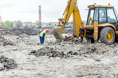 Workers are working manually next to the excavator, teamwork, ma Royalty Free Stock Images