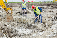Workers are working manually next to the excavator, teamwork, ma Royalty Free Stock Photos