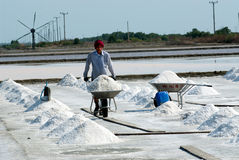 Workers are working at a salt farm in Thailand. SAMUTSONGKHRAM,THAILAND - FEB 18: Unidentified workers carrying salt at the salt farm on February 18,2014 in royalty free stock photos