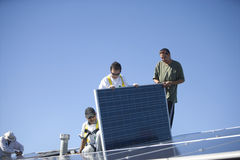 Workers Working On Solar Panel Against Blue Sky Royalty Free Stock Image