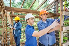 Workers Working In Wooden Cabin At Site Stock Photography