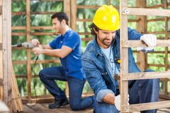 Workers Working In Wooden Cabin At Site Stock Image
