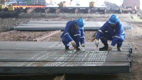 Workers writing id numbers on steel blocks. Workers writing id numbers on finished steel blocks by white paint stock footage
