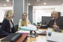 Workes de bureau parlant et regardant des dossiers : femmes et patron mûr au bureau photos libres de droits