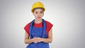 Worket femelle de construction expliquant ses idées à la caméra sur le fond de gradient banque de vidéos