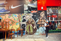 Worket of street cafe writing sms message on the background of graffiti and stores advertising Stock Photos