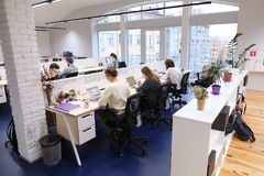Office space in middle of working day with people immersed in wo. Workforce, company`s employees are busy with their own affairs and work of modern office Royalty Free Stock Photo