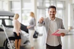 Workin de vendeur au concessionnaire automobile photos stock