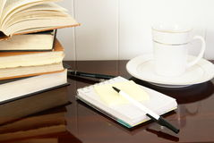Working. Office desk with notepads, pens, coffee and doughnuts Royalty Free Stock Photo