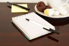 Working. Office desk with notepads, pens, coffee and doughnuts Royalty Free Stock Image
