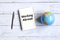 Working abroad. Top view of globe of world map,pen and notebook written with & x27;WORKING ABROAD& x27; on white wooden background stock image