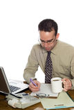 Working Accountant. A young accountant doing some work at his desk, isolated against a white background Stock Photos