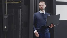 Man working with servers in modern data center using laptop