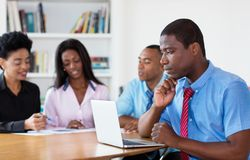 Working african american businessman with team and computer stock images