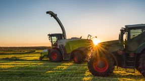 Working agicultural machinery in sunny day. Working agicultural machinery on a sunny spring day - sunset or sunrise Stock Image