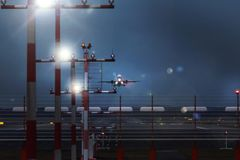 Working airport beacons with starting airplane in the evening. A working airport beacons with starting airplane in the evening Royalty Free Stock Photo