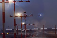 Working airport beacons with starting airplane in the evening. A working airport beacons with starting airplane in the evening Royalty Free Stock Photos