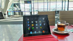 Working at Airport. With iPad while enjoying hot tea Stock Photography