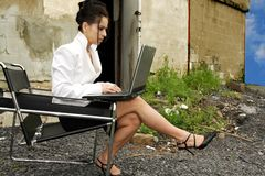 Working anywhere. Pretty women typing on her laptop outside royalty free stock photography