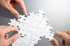Working on an arrow shaped jigsaw puzzle. Royalty Free Stock Images