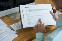 Working as a team of professionals on a project in the office, looking and researching. Trends in buying and selling or the stock market Stock Photography