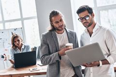 Working as a team. Two young modern men in smart casual wear using laptop while working in the creative office stock photo