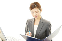 Working Asian business woman. Asian business woman sitting at desk working on laptop Royalty Free Stock Photos